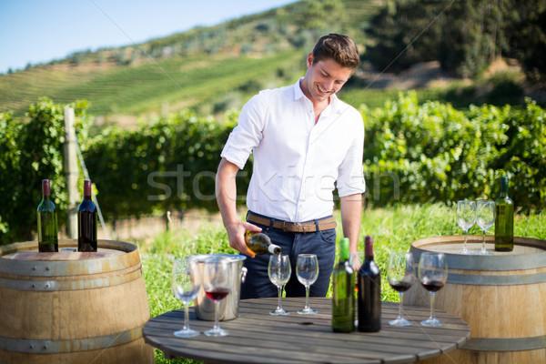 Smiling man pouring wine in glass on table Stock photo © wavebreak_media