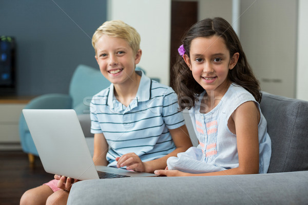 Mosolyog testvérek laptopot használ nappali portré otthon Stock fotó © wavebreak_media