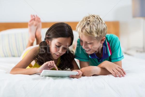 Mosolyog testvérek digitális tabletta ágy hálószoba Stock fotó © wavebreak_media