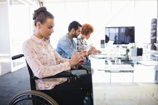 Businesswoman using digital tablet while sitting on wheelchair Stock photo © wavebreak_media
