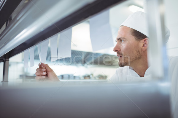 Chef looking at an order list in the commercial kitchen Stock photo © wavebreak_media