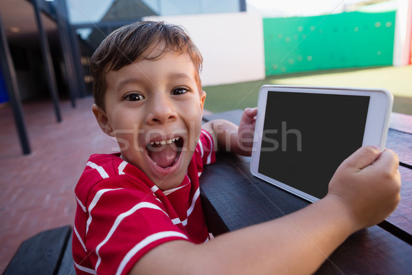 Portrait of cute boy holding digital tablet while sitting at table Stock photo © wavebreak_media