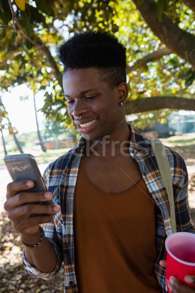 Stockfoto: Man · mobiele · telefoon · park · jonge · man · glas · kunst