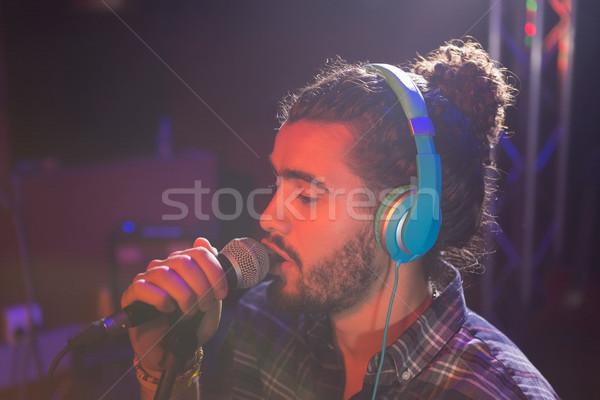 Homme écouter casque chanter micro discothèque Photo stock © wavebreak_media