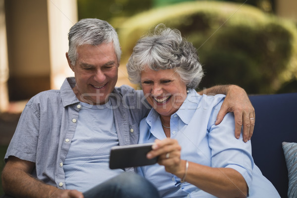 Cheerful senior couple looking at mobile phone in backyard Stock photo © wavebreak_media