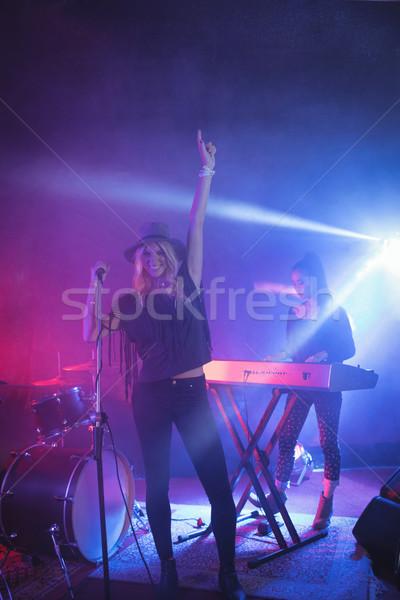Cheerful singer singing while musician playing piano in illuminated nightclub Stock photo © wavebreak_media
