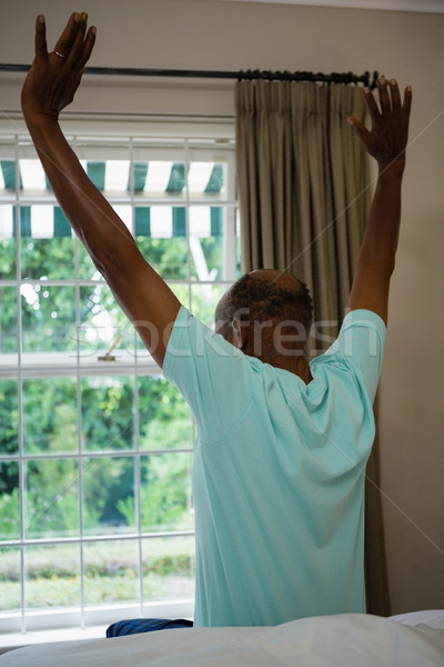 Rear view senior man stretching arms while sitting on bed Stock photo © wavebreak_media