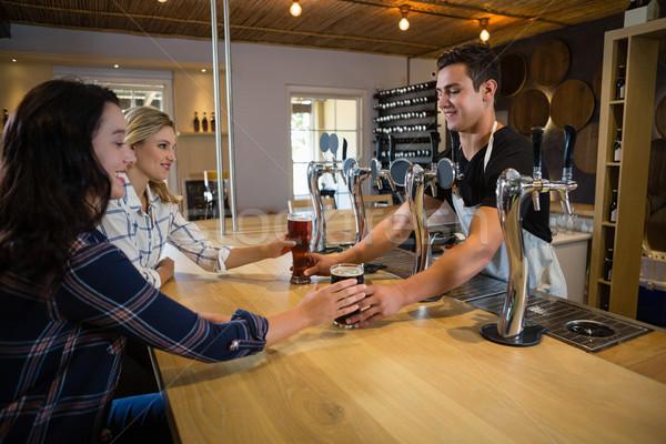 Bartender serving drinks to female friends Stock photo © wavebreak_media