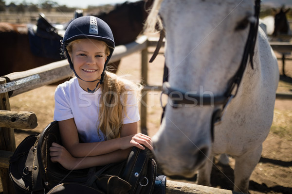 Smiling girl leaning on the fence in ranch Stock photo © wavebreak_media