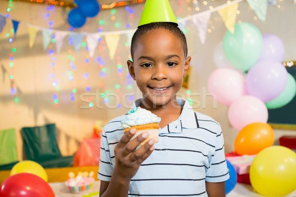 Portrait of cute boy holding cupcake during birthday party Stock photo © wavebreak_media