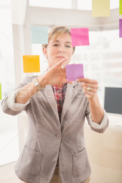 Casual businesswoman putting sticky notes on glass Stock photo © wavebreak_media