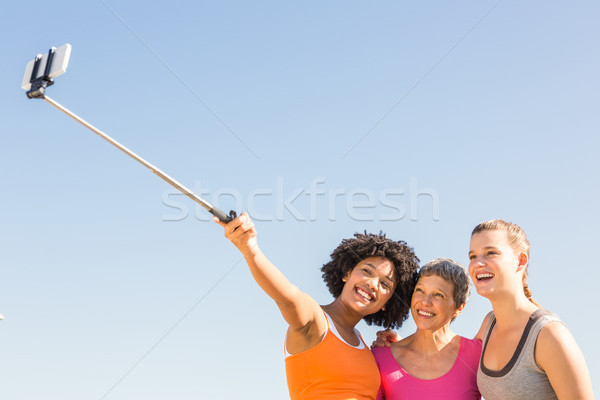 Smiling sporty women taking selfies with selfiestick  Stock photo © wavebreak_media