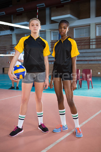 Female players standing together with ball in the volleyball court Stock photo © wavebreak_media