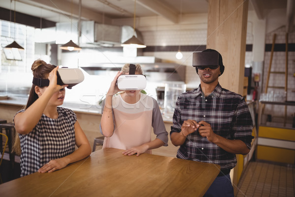 Young friends sitting with virtual reality headsets at coffee shop Stock photo © wavebreak_media