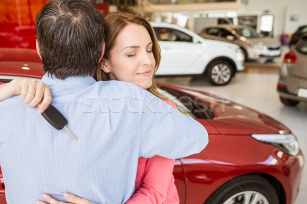 Smiling woman holding key while hugging her husband  Stock photo © wavebreak_media