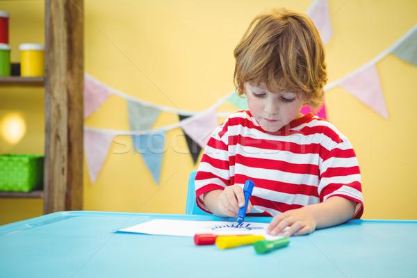 Smiling boy colouring some paper Stock photo © wavebreak_media