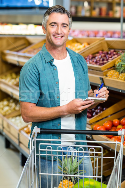 Smiling man looking at his list Stock photo © wavebreak_media