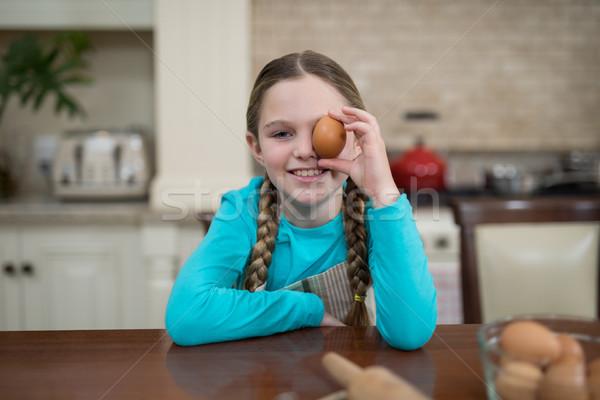 Lány tart tojás ül asztal konyha Stock fotó © wavebreak_media