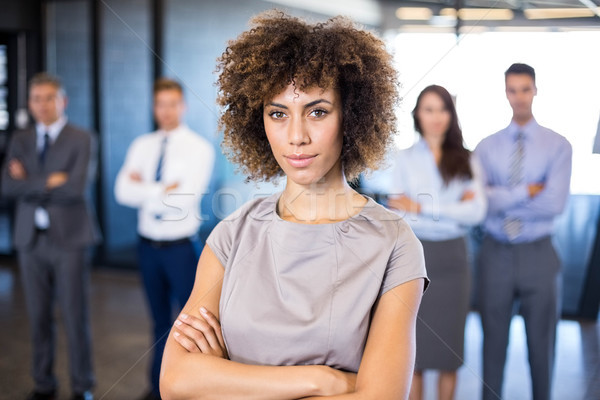 Stock photo: Businesswoman smiling at camera while her colleagues standing in