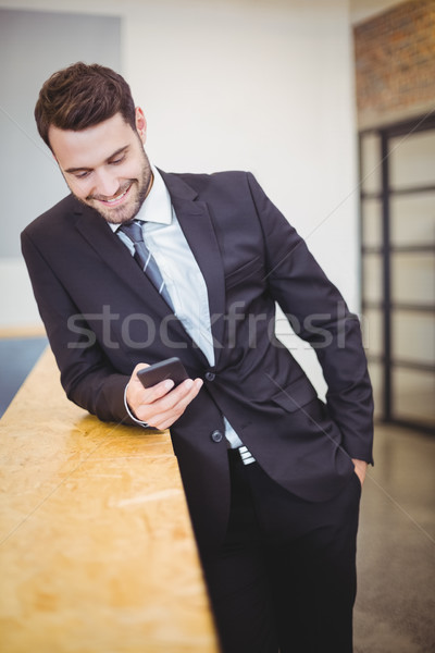 Businessman looking in cellphone while leaning on counter Stock photo © wavebreak_media