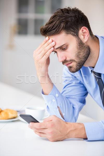 Tensed businessman using mobile phone by table Stock photo © wavebreak_media