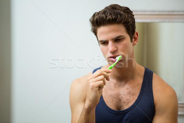 Young man brushing his teeth in bathroom Stock photo © wavebreak_media