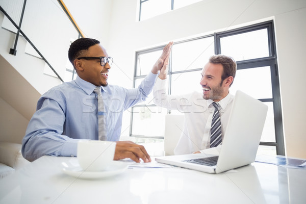 Businessmen giving a high five while at a meeting Stock photo © wavebreak_media