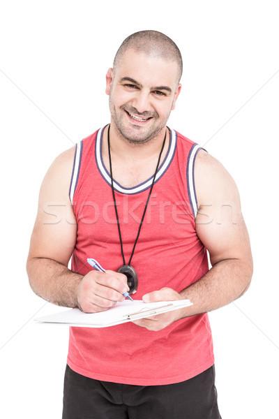 Athlete writing on clipboard Stock photo © wavebreak_media