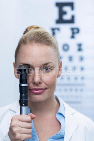 Female optometrist looking through ophthalmoscope Stock photo © wavebreak_media
