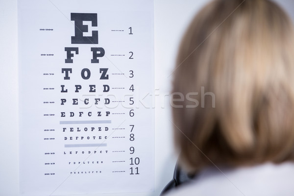 Optometrist looking at eye chart Stock photo © wavebreak_media