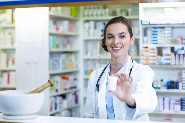 Smiling pharmacist showing medicine container in pharmacy Stock photo © wavebreak_media