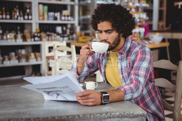 Stock photo: Man reading newspaper while having coffee
