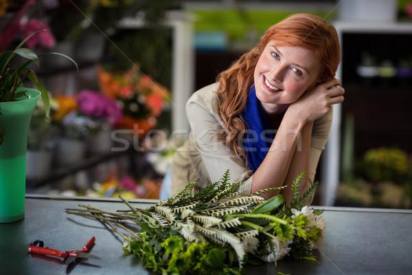 Happy female florist leaning in flower shop Stock photo © wavebreak_media