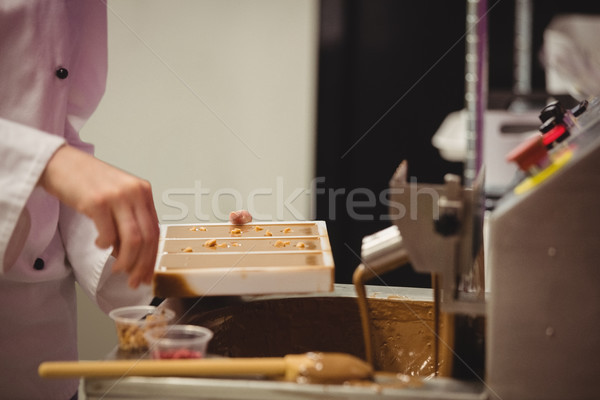 Stock photo: Worker sprinkling confectionary on chocolate mould