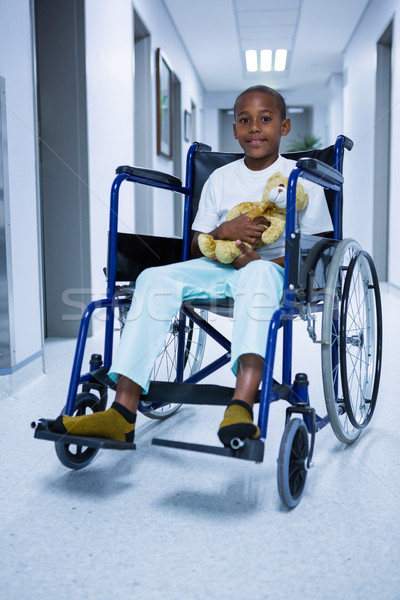 Portrait of boy sitting on wheelchair and holding teddy bear in corridor Stock photo © wavebreak_media