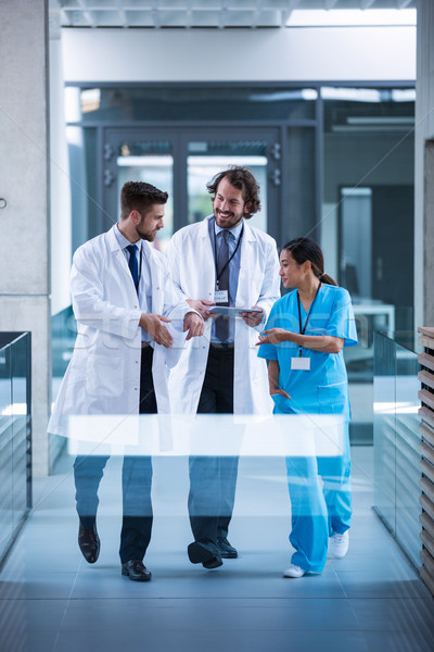Stock photo: Doctor holding digital tablet having a discussion with colleagues