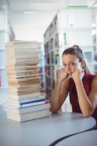 Sad schoolgirl looking at stack of books in library Stock photo © wavebreak_media