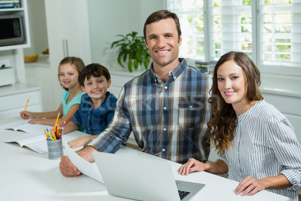 Smiling parents working with laptop and childrens studying in living room at home Stock photo © wavebreak_media