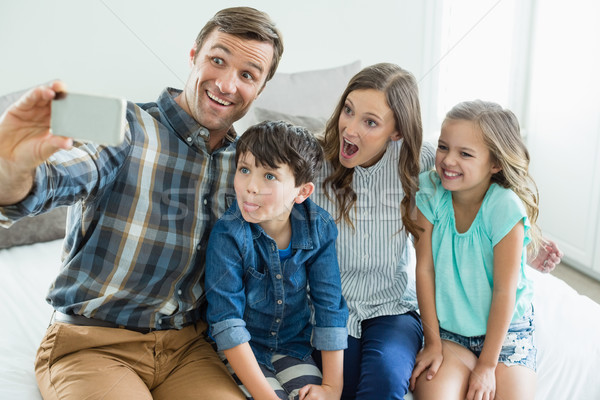 Stock photo: Smiling man taking selfie with family while sitting in bedroom