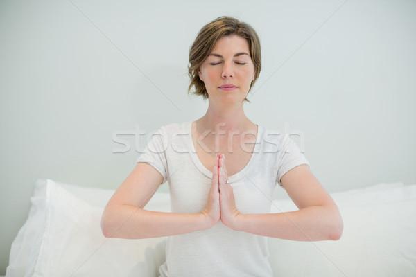Woman doing meditation on bed in bedroom Stock photo © wavebreak_media