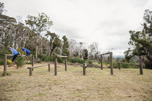 People jumping over the hurdles during obstacle course Stock photo © wavebreak_media