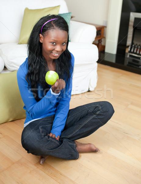 Happy woman eating an apple sitting on the floor Stock photo © wavebreak_media