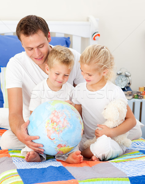 Jolly father and his children holding a terretrial globe  Stock photo © wavebreak_media