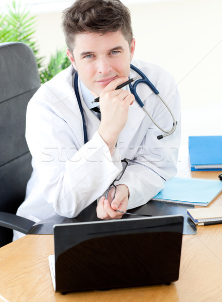 Smiling male doctor using a laptop sitting at his desk  Stock photo © wavebreak_media