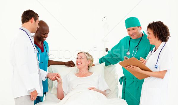 Elderly woman between a medical team against white background Stock photo © wavebreak_media