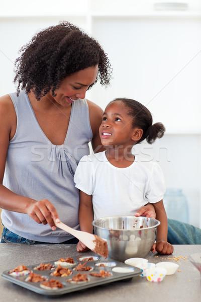 Happy mother helping her daughter cooking biscuits in the kitchen Stock photo © wavebreak_media