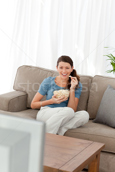 Woman laughing while watching a movie on television in the living room Stock photo © wavebreak_media