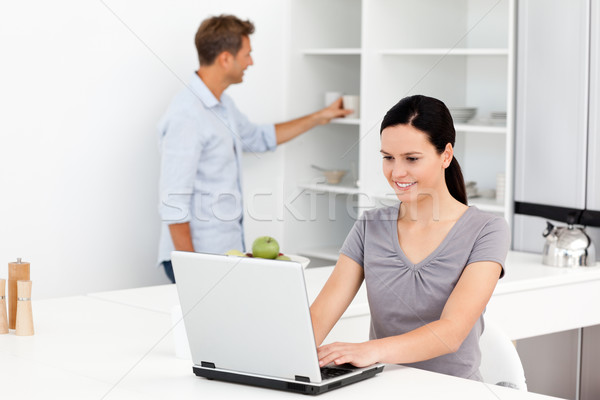 Cute woman working on the laptop in the kitchen while her boyfriend standing in the background Stock photo © wavebreak_media