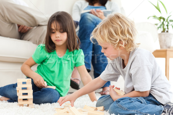 Cute brother and sister playing with dominoes on the floor in the living room Stock photo © wavebreak_media