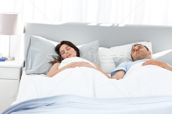 Lovely couple holding their hands while sleeping on their bed Stock photo © wavebreak_media
